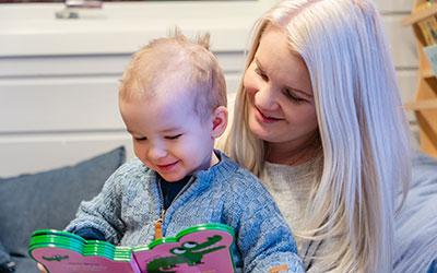 Bilde av en barnehageansatt som leser bok til en liten gutt