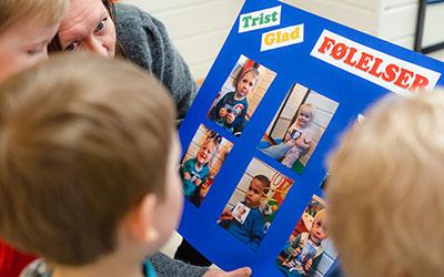 Bilde av barn som ser på en plakat
