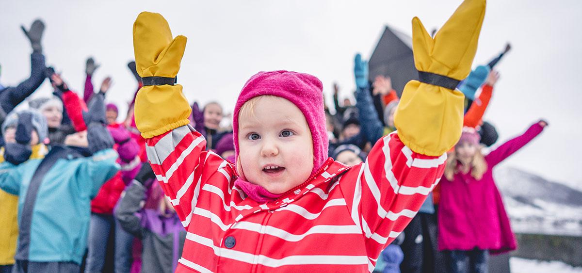 Bilde av ei lita jente som strekker armene i været