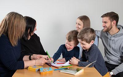 Bilde av 4 voksne og 2 barn rundt et bord